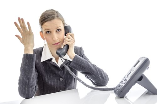 Impatient business woman at white desk making a phone call.